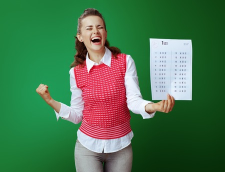 smiling young learner woman in grey jeans and pink sleeveless shirt with A+ test result rejoicing isolated on chalkboard green background. 免版税图像