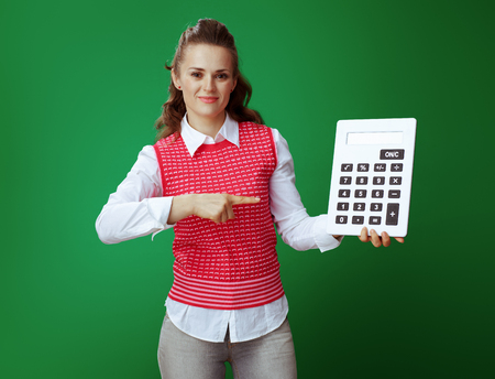happy young student in grey jeans and pink sleeveless shirt pointing at big white calculator against green background. Finances and expenditures of modern education. Stock fotó
