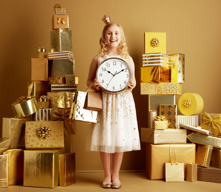 Full length portrait of happy young girl in beige fit and flare dress and a little crown on head with gold shopping bags and round clock among 2 piles of golden gifts in front of a plain wall.