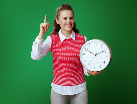 happy modern learner woman in grey jeans and pink sleeveless shirt with white round clock draws attention to something isolated on green. Importance of time management in modern educations. 免版税图像