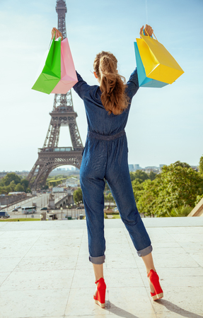 Seen from behind modern tourist woman in blue jeans overall with shopping bags rejoicing not far from Eiffel tower in Paris, France.