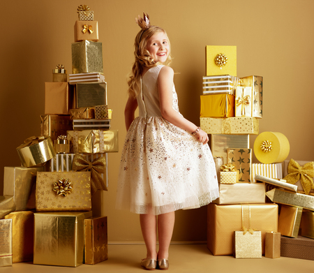 Full length portrait of smiling modern girl in beige fit and flare dress and a little crown on head among 2 piles of golden gifts in front of a plain wall looking back. unique birthday gifts.