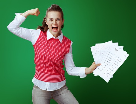 happy modern student in grey jeans and pink sleeveless shirt showing A+ test results and biceps isolated on chalkboard green background.