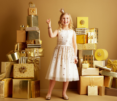 Full length portrait of smiling young girl in beige fit and flare dress and a little crown on head fingers snapping among 2 piles of golden gifts in front of a plain wall. deals, sales, discounts.
