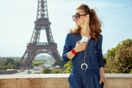 happy stylish tourist woman in blue jeans overall with smartphone using multimedia programs in Paris, France. 写真素材