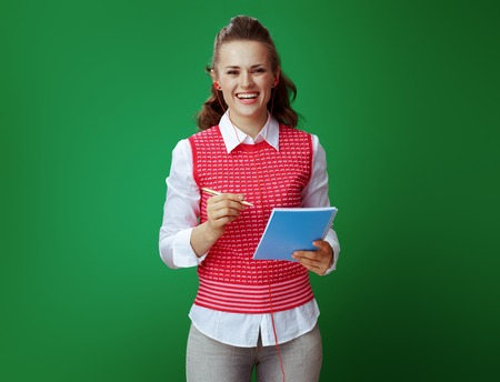smiling modern learner woman in grey jeans and pink sleeveless shirt in headphones taking notes in blue notebook isolated on green background. Modern education with listening to audio materials.
