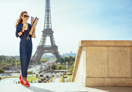 Full length portrait of happy trendy traveller woman in blue jeans overall with coffee cup and two baguettes walking against Eiffel tower in Paris, France. Stock Photo