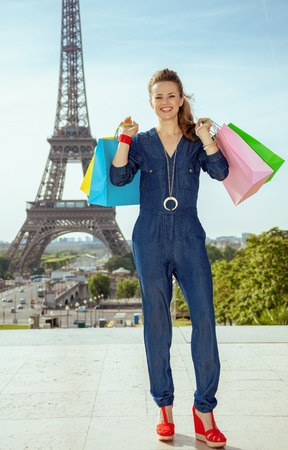 Full length portrait of smiling stylish traveller woman in blue jeans overall with shopping bags against Eiffel tower in Paris, France.