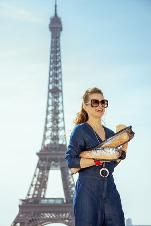 happy stylish woman in blue jeans overall with coffee cup and two baguettes looking into the distance in Paris, France. 版權商用圖片