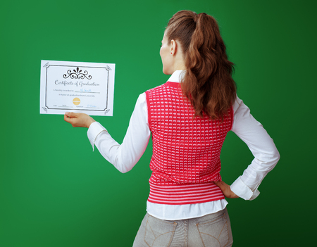 Seen from behind young student woman in grey jeans and pink sleeveless shirt looking at Certificate of Graduation isolated on green background.