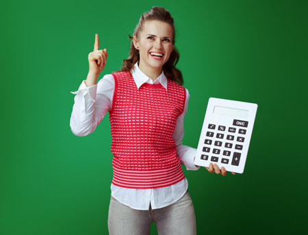 smiling healthy student woman in grey jeans and pink sleeveless shirt with big white calculator got idea isolated on green. Finances and expenditures of modern education under control Stock fotó - 117984717