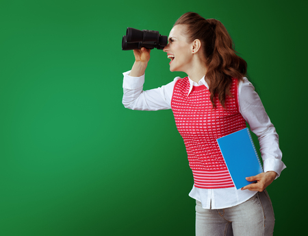smiling healthy student woman in grey jeans and pink sleeveless shirt with a blue notebook looking into the distance through binoculars isolated on green background. looking for opportunities
