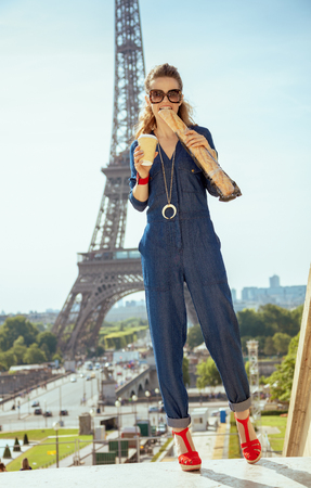 Full length portrait of modern woman in blue jeans overall with coffee cup eating baguette not far from Eiffel tower in Paris, France. 写真素材