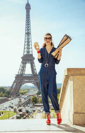Full length portrait of smiling elegant tourist woman in blue jeans overall with coffee cup and two baguettes not far from Eiffel tower in Paris, France. Reklamní fotografie
