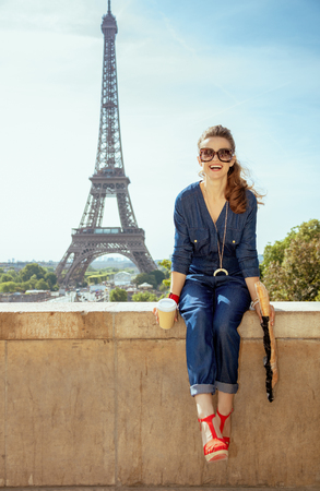 Portrait of happy trendy tourist woman in blue jeans overall with coffee cup and baguette having excursion against clear view of the Eiffel Tower in Paris, France.