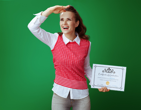 happy healthy student woman in grey jeans and pink sleeveless shirt with Certificate of Graduation looking into the distance against chalkboard green background. Looking in successful future 版權商用圖片