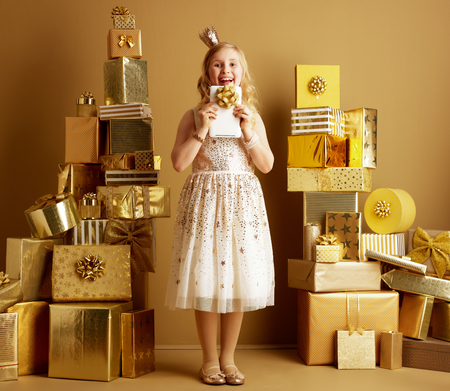 Full length portrait of happy young girl in beige fit and flare dress and a little crown on head looking out from tablet PC with bow among 2 piles of golden gifts in front of a plain wall. 스톡 콘텐츠