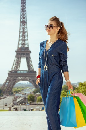 smiling stylish tourist woman in blue jeans overall with shopping bags looking into the distance in Paris, France. Stock Photo
