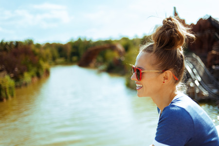 smiling healthy solo traveller woman in blue t-shirt on river boat exploring countryside while having river cruise. Banco de Imagens