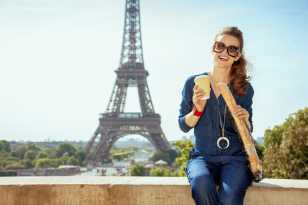 Portrait of smiling elegant woman in blue jeans overall with coffee cup and baguette not far from Eiffel tower in Paris, France. Stock Photo