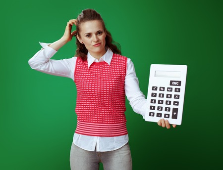 doubting modern student in grey jeans and pink sleeveless shirt with big white calculator scratching head isolated on green background. Financial challenges and expenditures of modern education.