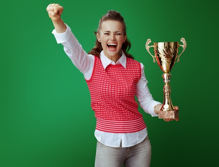 smiling fit learner woman in grey jeans and pink sleeveless shirt with golden goblet rejoicing isolated on green background. challenging education
