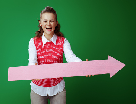 happy fit learner woman in grey jeans and pink sleeveless shirt giving big pink arrow pointing right isolated on green background. Banco de Imagens