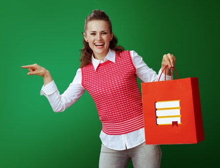 smiling fit learner woman in grey jeans and pink sleeveless shirt with red shopping bag with books pointing at something isolated on chalkboard green background. bookstore or stationery store