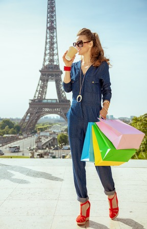 Full length portrait of smiling elegant tourist woman in blue jeans overall with shopping bags drinking coffee against clear view of the Eiffel Tower in Paris, France.