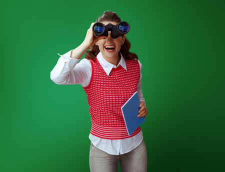happy modern learner woman in grey jeans and pink sleeveless shirt with a blue notebook looking in camera through binoculars isolated on green background. Consider far perspectives after degree