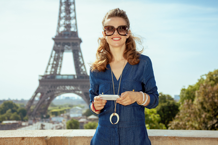 happy young traveller woman in blue jeans overall using smartphone for info sharing and networking against Eiffel tower in Paris, France.