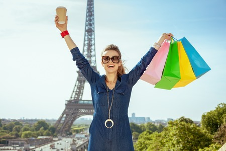 Portrait of happy young traveller woman in blue jeans overall with shopping bags and coffee cup rejoicing in the front of Eiffel tower in Paris, France.