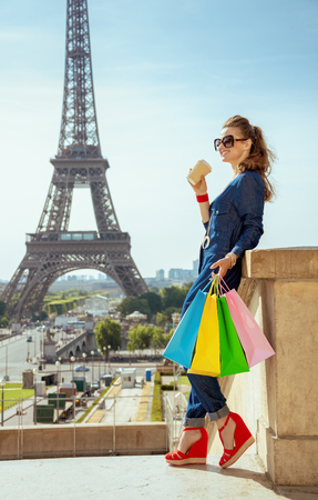 Full length portrait of smiling young traveller woman in blue jeans overall with shopping bags and coffee cup looking into the distance in the front of Eiffel tower in Paris, France.