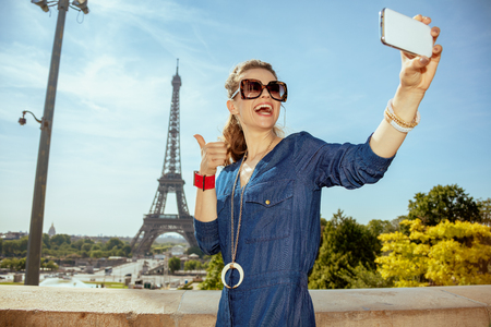 happy trendy woman in blue jeans overall showing thumbs up and taking selfie with smartphone in Paris, France.