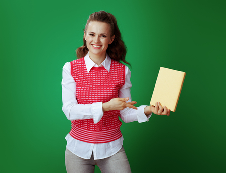 happy fit student in grey jeans and pink sleeveless shirt pointing at a yellow book isolated on chalkboard green.