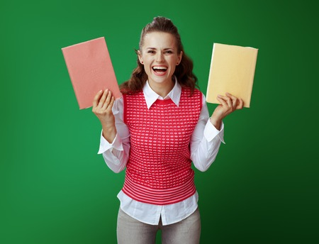 happy fit student woman in grey jeans and pink sleeveless shirt showing two red and yellow books isolated on chalkboard green background. Stock Photo