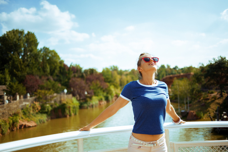 relaxed fit woman in blue t-shirt on river boat enjoying river cruising.