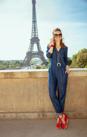 Full length portrait of smiling stylish woman in blue jeans overall not far from Eiffel tower in Paris, France speaking on a cell phone.
