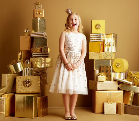 Full length portrait of happy elegant girl in beige fit and flare dress and a little crown on head among 2 piles of golden gifts in front of a plain wall. efficiency shopping in one place concept.