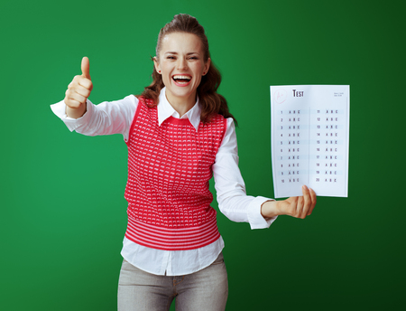 smiling young student in grey jeans and pink sleeveless shirt showing A+ exam result against green background. Banco de Imagens