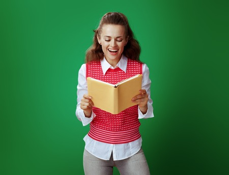 surprised healthy learner woman in grey jeans and pink sleeveless shirt reading yellow book isolated on green.