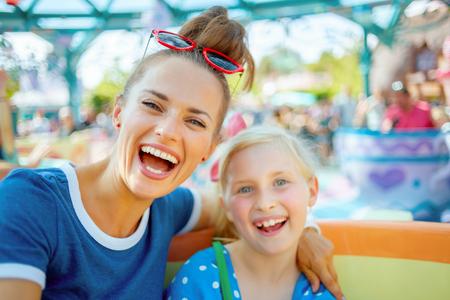 Portret van glimlachende moderne moeder en kindtoeristen in themapark die van aantrekkelijkheid genieten.