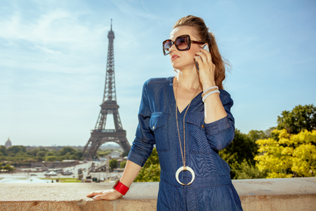 elegant woman in blue jeans overall not far from Eiffel tower in Paris, France speaking on a mobile phone. 写真素材