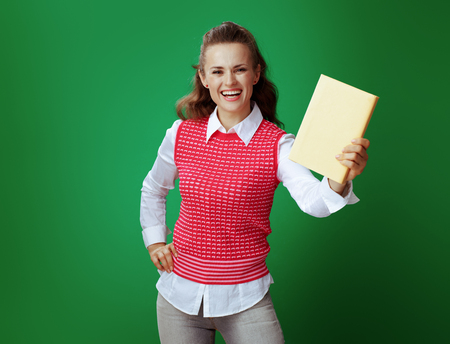 smiling fit student in grey jeans and pink sleeveless shirt showing a yellow book on green background.