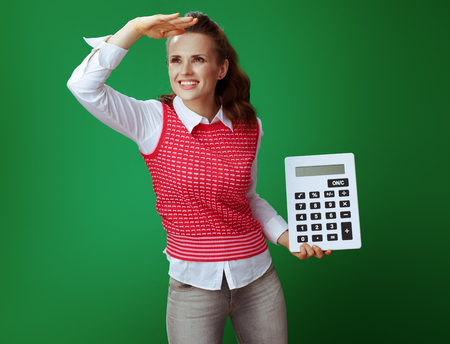 smiling fit learner woman in grey jeans and pink sleeveless shirt with big white calculator looking into the distance isolated on green background. Finances and expenditures of modern education. Stock fotó