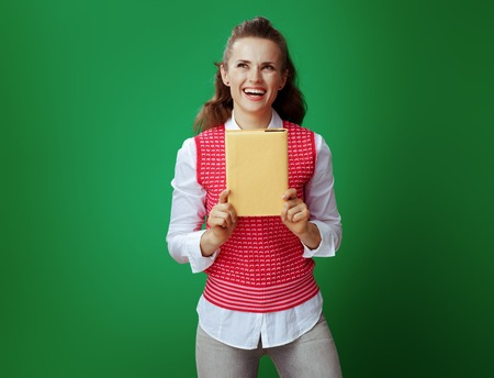 smiling modern student woman in grey jeans and pink sleeveless shirt with a yellow book looking aside on green background. Stok Fotoğraf - 117810450