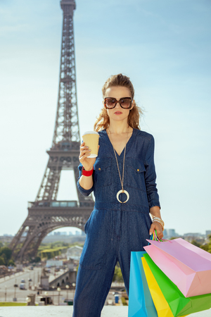 trendy traveller woman in blue jeans overall with shopping bags and coffee cup at Trocadero overlooking Eiffel tower in Paris, France.