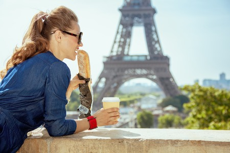 smiling elegant traveller woman in blue jeans overall with coffee cup eating baguette having excursion against clear view of the Eiffel Tower in Paris, France.