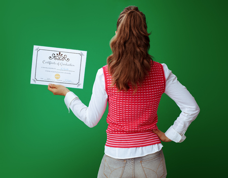 Seen from behind fit student in grey jeans and pink sleeveless shirt with Certificate of Graduation isolated on green. Stok Fotoğraf