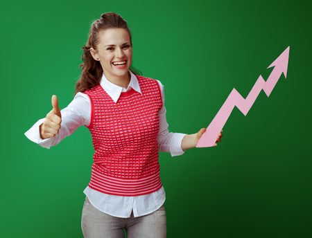 smiling modern student in grey jeans and pink sleeveless shirt with a rising graphics arrow showing thumbs up isolated on green. Economy college illustration